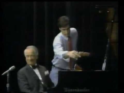Victor Borge takes help from another man when he has trouble playing the piano and turning the sheetmusic at the same time.