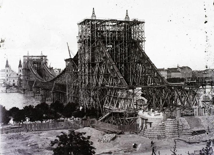 az épülő Erzsébet híd, szemben a pesti hídfőnél a Belvárosi templom.