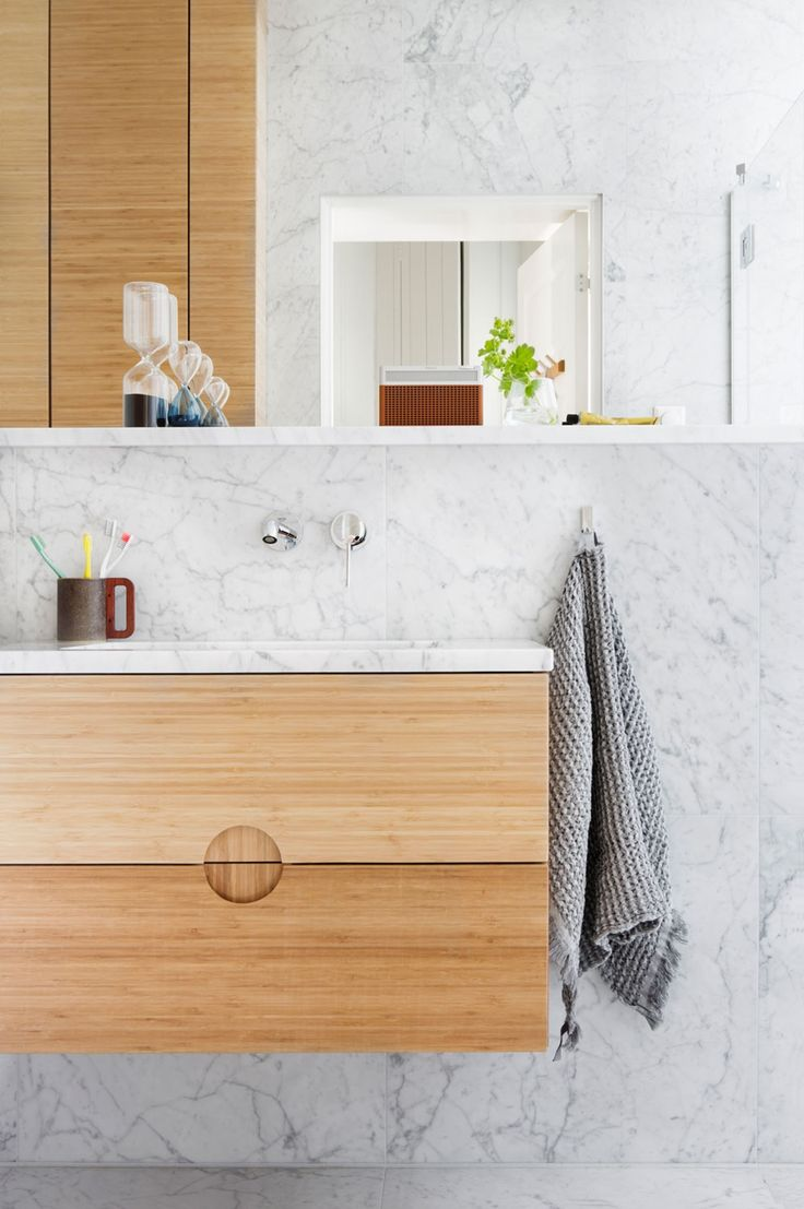 While marble gives this bathroom a luxury feel, vanity unit in bamboo. The hourglass on the shelf is from Granit, the Geneva radio is from Lefdal, the towel from Hay and the cup from Matímanana.