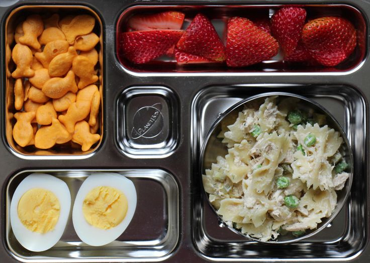 Planet Box container and a healthy school lunch Gold fish crackers, strawberries, hard boiled egg and tuna, pea, pasta salad.