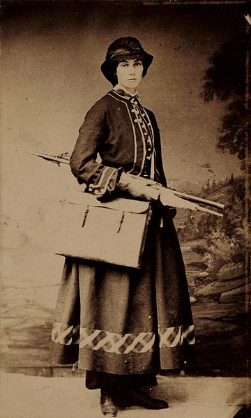 Portrait of Fidelia Bridges with portable easel and painting supplies standing in front of false background of a landscape. Fidelia Bridges, ca. 1864 / unidentified photographer.