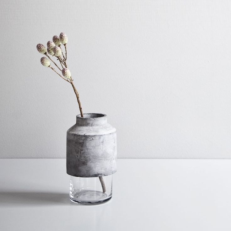 This vase is actually composed of two pieces - a cast concrete tube that can be removed from the cylindrical vase in which it sits. The vase was designed and produced by Danish design company, Menu.