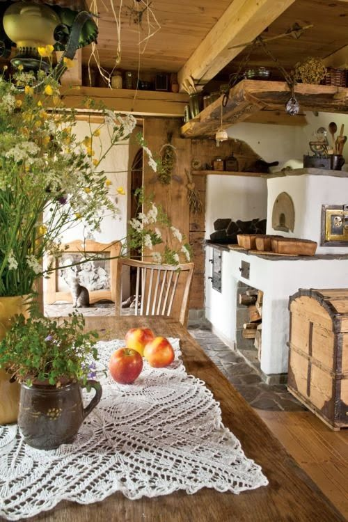 Fabulous kitchen!  Again, the plants - as well as a wood stove, bread oven, hanging beams for shelves overhead, and a wonderful big country wooden table.