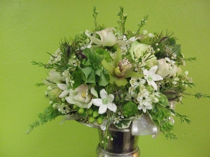 Green cymbidium orchids, bells of Ireland, hypericun berries, and button mums are teamed with white calla lilies, hydrangea, freesia, star of Bethlehem, waxflower, and stephanotis featuring green beaded centers.