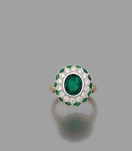 BAGUE EMERAUDE ENTOURAGE  L'émeraude ovale en sertissure est entourée de diamants taille brillant et tsavorites calibrées à bordure dentelée. Monture en or gris 18K.  Poids brut : 6,5 gr.  Poids de l'émeraude : 1,50 carat environ.  TDD : 53  Estimation 2.500/3.000€