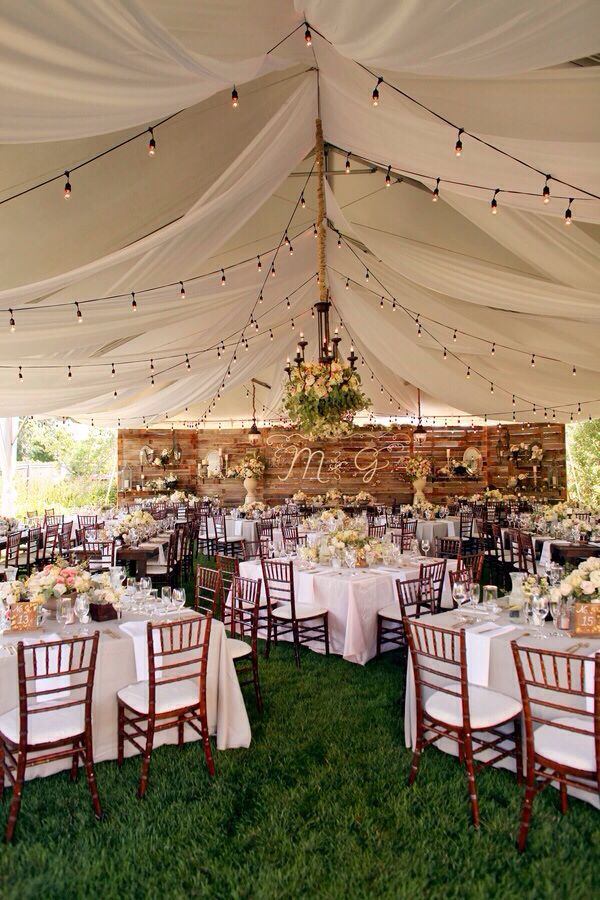 We love this outdoor backyard-chic tented wedding! For wedding makeup, hair accessories, and more, visit Beauty.com.