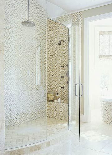 A seamless curved door on this two-person shower allows natural light to flood the area and showcases the tiled walls. The neutral color of the mosaic tiles brings serenity to the room. The area's limestone floor isn't just an attractive surface; it's heated for comfort.