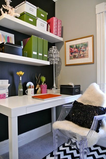 small office defined by navy wall behind  shelves, darling