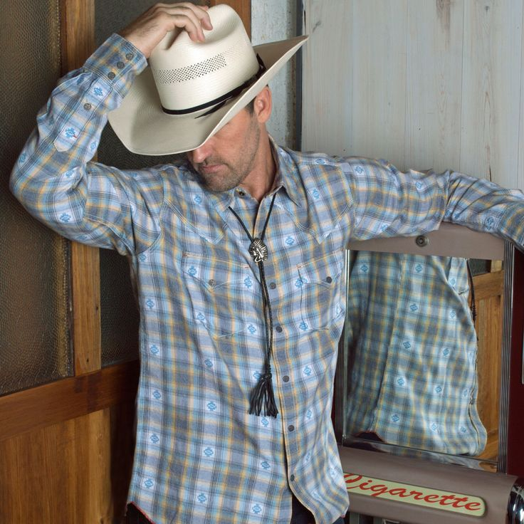Modern cowboy in a Ryan Michael plaid shirt with a bolo tie and straw cowboy hat.