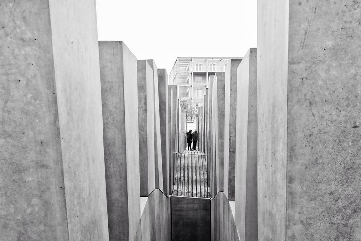 """The Memorial to the Murdered Jews of Europe, also known as the Holocaust Memorial, is a memorial in Berlin to the Jewish victims of the Holocaust, designed by architect Peter Eisenman and engineer Buro Happold. It consists of a 19,000 m2 (4.7-acre) site covered with 2,711 concrete slabs or """"stelae"""", arranged in a grid pattern on a sloping field. The stelae are 2.38 m (7 ft 10 in) long, 0.95 m (3 ft 1 in) wide and vary in height from 0.2 to 4.8 m (7.9 in to 15 ft 9.0 in)."""