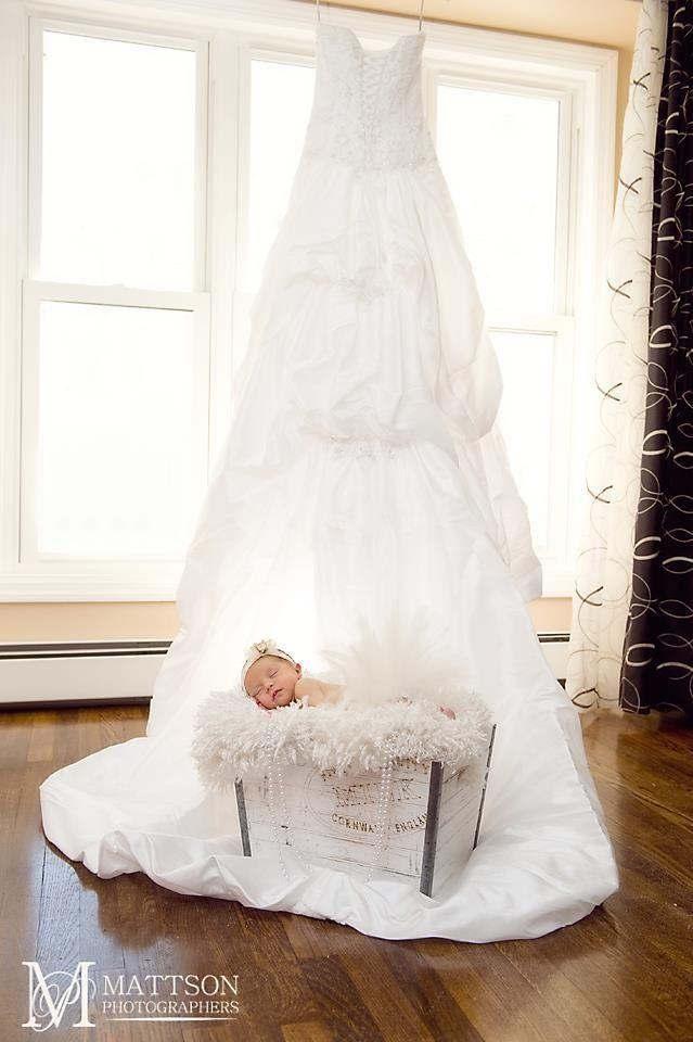 Baby girl with mom's wedding dress.