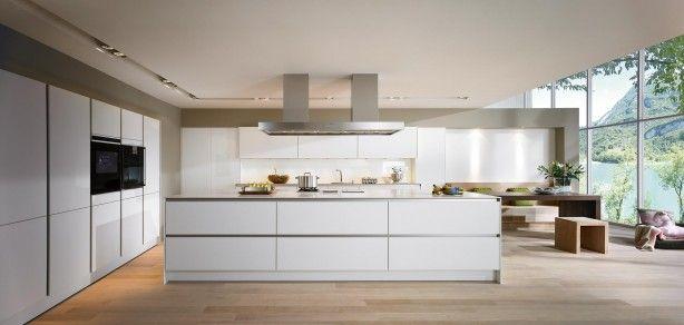 Strenge moderne keuken met groot kookeiland. De strenge symmetrie van deze SieMatic S2 keuken geeft de hele kamer rust en een modern karakter. De opvallende grote eiland heeft aan twee kanten kasten en heeft een zee van opbergruimte die goed is te bereiken dankzij de zeer brede lades. De strenge symmetrie wordt voorgezet boven het kookeiland in vorm van een de dubbel afzuigkap.