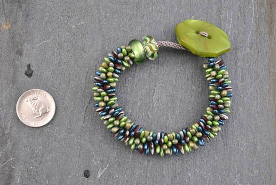 Green/Burgundy/Teal Kumihimo Artisan Bracelet #bracelet #kumihimo #kumihimobracelet #artisan #artisanbracelet #oneofakind #handmade #woven #handwoven #knotted #handknotted #boho #bohemian #lampwork #lampworkbeads #foil #feathered #marbled #marbledbutton #spiky #rizo #rizobeads #drop #dropbeads #celadon #green #teal #burgundy #bronze #iridescent #flexible #lightweight #textured #japanese #weaving #japaneseweaving