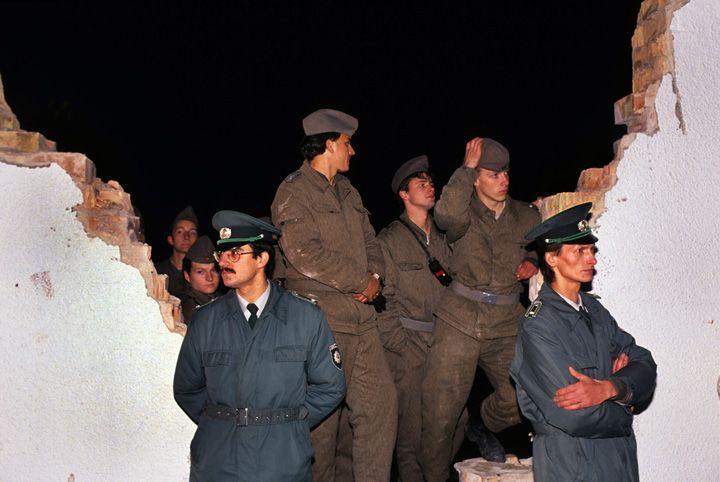 Chris Niedenthal | Żołnierze NRD pracują nad wyrwą w Murze przy Bernauer Strasse we Wschodnim Berlinie; muszą zdążyć do rana, by nowe przejście było gotowe. Straż graniczna stoi przed Murem, by nie dopuścić do przejścia przez oficjalnym otwarciem | Listopad 1989