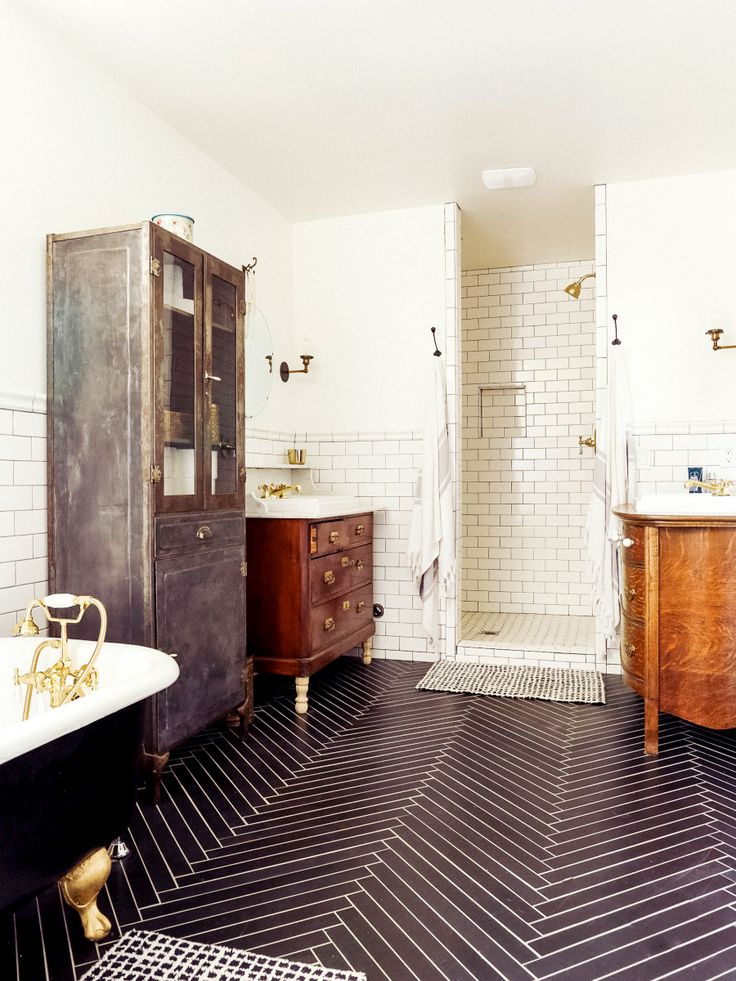 Tiled bathroom with subway tiles in shower and herringbone pattern on floor, country-chic industrial furniture