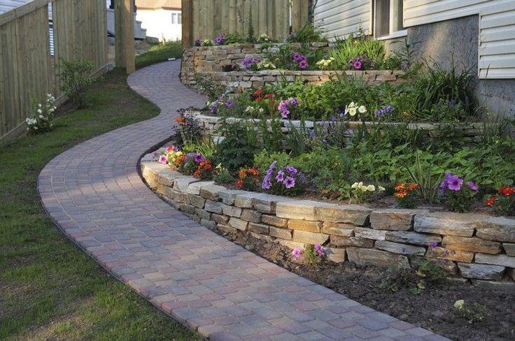 aménagement jardin en pente, murs de soutènement en pierre, pétunias et fleurs et allée en pavés