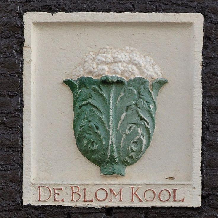 """Palmgracht 63, Amsterdam  In 1679, zo blijkt uit een kwijtschelding, staat """"de Blomkool"""" in de gevel van Palmgracht 63. Opvallend aan deze kwijtschelding is dat de naam van de eigenaar van de belendende panden Willem Harmensz Cool is en dat in het huis aan de oostzijde (het huidige nr. 61) """"de Kool"""" in de gevel staat.   Het valt aan te nemen dat toen in de gevel van het huis aan de westzijde (het huidige nr. 65) ook een gevelsteen met een kool in de gevel stond. Dit leiden we af uit de…"""