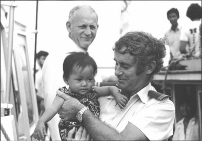 Customs Officer Frank Dalton holding a Vietnamese refugee child, Xye Than Hueon…