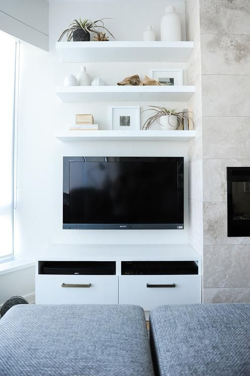 Gray stools face three styled white floating shelves fixed above a wall mounted flat panel television positioned above white television cabinets located next to a cream stone fireplace.