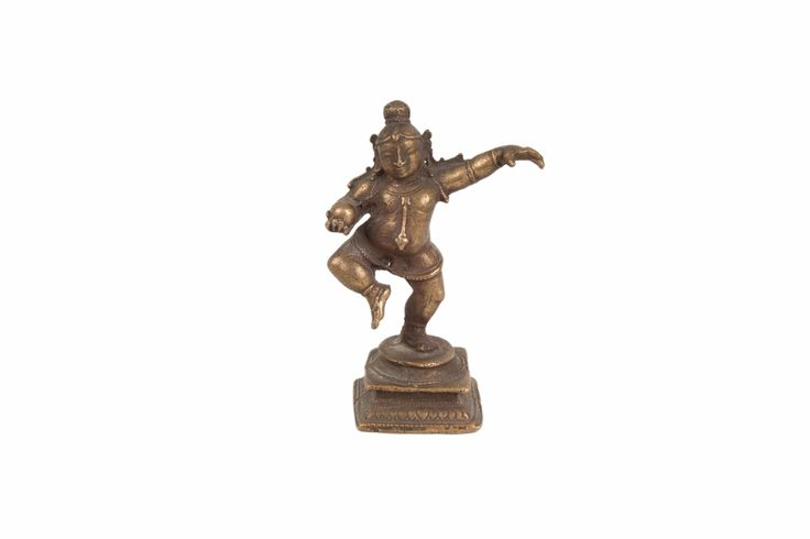 Description A small bronze figure of Krishna in 17th/18th century style, South India. Krishna is depicted naked, wearing only a girdle, anklets, bracelets, a necklace, armlets, earrings. The figure dancing, standing on slightly bent left leg, with the right leg raised, stretching out (pataka) the left arm, while holding a butter ball in his right hand. His hair pulled back and tied into a bun.  Date 20th century  www.collectorstrade.de