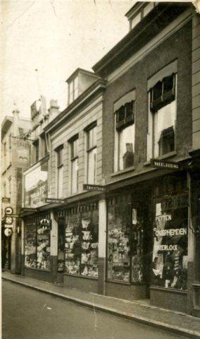 Beschrijving: De winkel van de Firma Leusen Engeln, ofwel Magazijn De Ooievaar aan de Hoogstraat 144 (links), 142 en 140 (rechts). Periode van de foto: tussen juni 1938 en eind 1949. Pand 144: geheel boven een uithangbord met de tekst: VAN DELFT'S KINDERWAGENS. Op het uithangbord beneden: MIDZA Op de winkelruit VAN 144: KOOPT IN DE OOIEVAAR VOOR BABY HIER. Op de winkelruit van 142: ALLES WAT BABY NODIG HEEFT. Op de winkelruit van 140:
