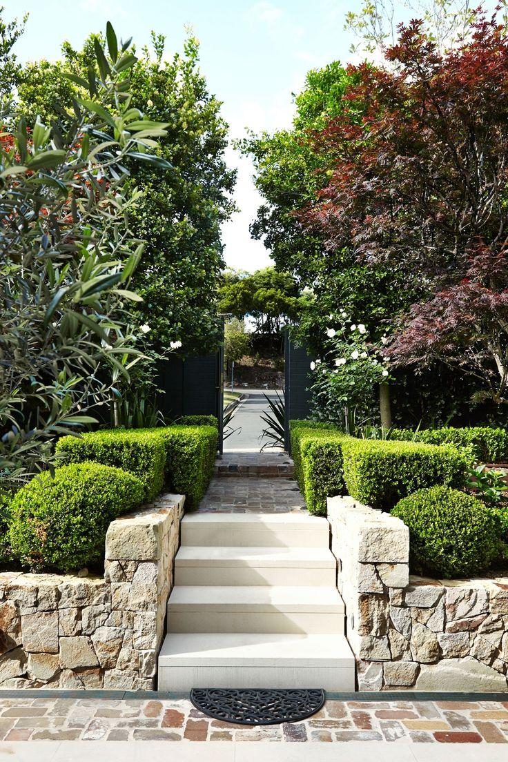 Sandstone walls + foliage frame an entrance - Outdoor Establishments