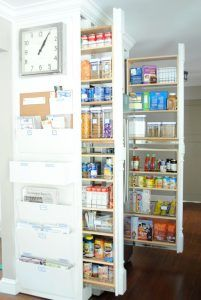 A creative pull-out built-in pantry. This one is not the usual front-facing shelves; instead, it's designed sideways. The white parts on the end of the shelves serve as the handles for pulling the shelves out, but when they're pushed in they just look like elegantly coffered wall design. No one would ever expect to find groceries hidden inside this wall!