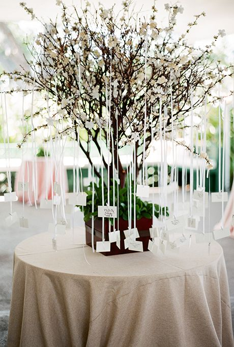 Brides.com: . Hang escort cards from a miniature tree for a striking display that becomes part of your décor.