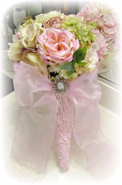 Our large tussie mussies make stunning bridal bouquets or can be hung on a wall or displayed on a table. A swirl of elegant pink fabrics embellishes the cone along with a hand dyed organza sash and vi