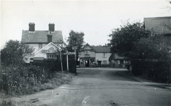 Canvey Island, Essex, England c.1925.  The village looking east. The Red Cow (now the King Canute) public house on the left, the thatched-roof water pump can just be seen on the right and the building in the middle is still standing today.