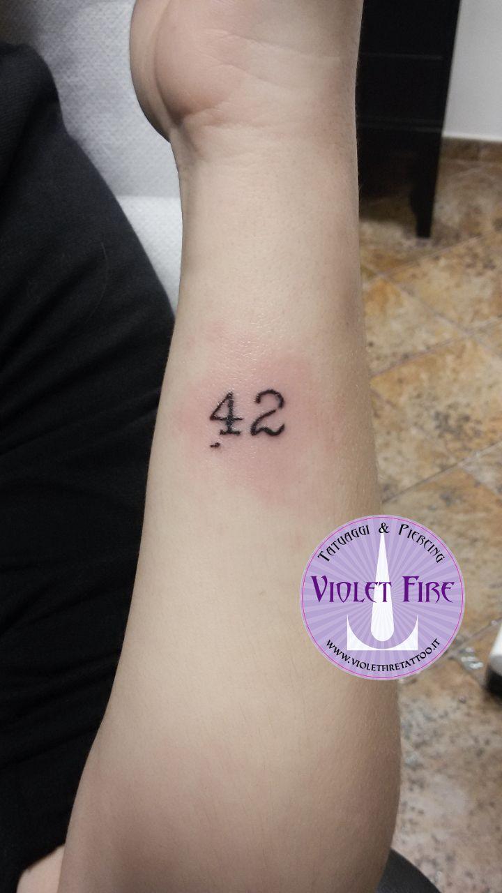 tatuaggio piccolo, tatuaggio scritta su braccio - 42 - guida galattica per autostoppisti - Violet Fire Tattoo - tatuaggi maranello, tatuaggi modena, tatuaggi sassuolo, tatuaggi fiorano - Adam Raia