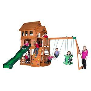 the liberty ii backyard play set has an awesome raised clubhouse topped by a wooden roof with bay windows dormers and a covered front porch