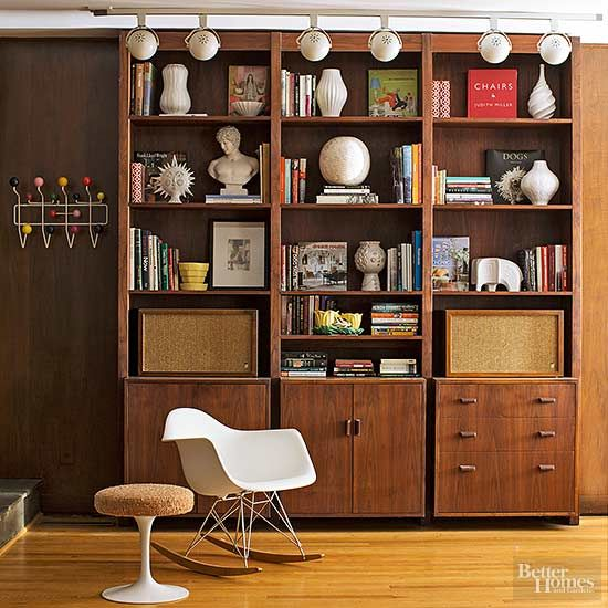 The den's built-in walnut bookcase and oversize track lighting are original to the house and required only a little cleaning to make them shine. The homeowners used the stage to display a number of new and vintage collectibles, including Jonathan Adler ceramics, an Eames rocker, and a vintage Saarinen Tulip side table with the original upholstered top./