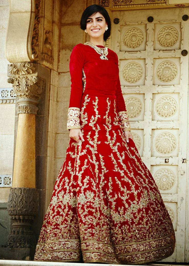 Scarlet red velvet gown encrusted with delicate thread embroidery by Kalki Fashion.