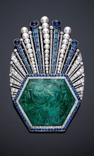 An aigrette turban ornament, designed by Paul Iribe and made by Robert Linzeler, circa 1910. Platinum, set with a carved emerald, sapphires, diamonds and pearls.