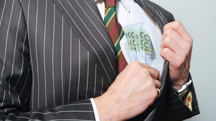 Ein Mann steckt sich 100-Euro-Scheine in die Tasche