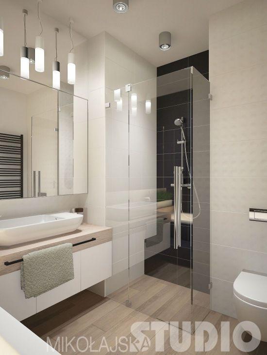 Aranżacja łazienki jest całkiem nowoczesna i schludna. Przezroczysta kabina prysznicowa podkreśla ten styl oraz spełnia praktyczną funkcję - pozwala optycznie powiększyć przestrzeń.