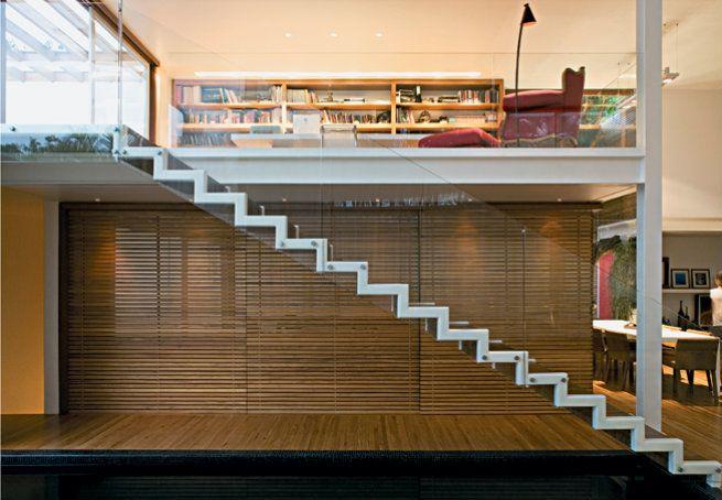 Leve e solta, a escada metálica dá acesso ao mezanino, com estrutura de vigas de aço, onde fica a biblioteca protegida por guarda-corpo de vidro temperado. Embaixo, painéis deslizantes de madeira ripada fecham a cozinha. O projeto é do escritório Bernardes Jacobsen