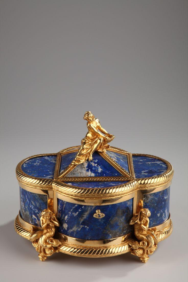 Une superbe boîte à bijoux polylobée en lapis-lazuli et monture en bronze doré, ciselé de côtes torses, sommée d'une pyramide soutenant une nymphe dénudée, les jambes couvertes par... 9,300€