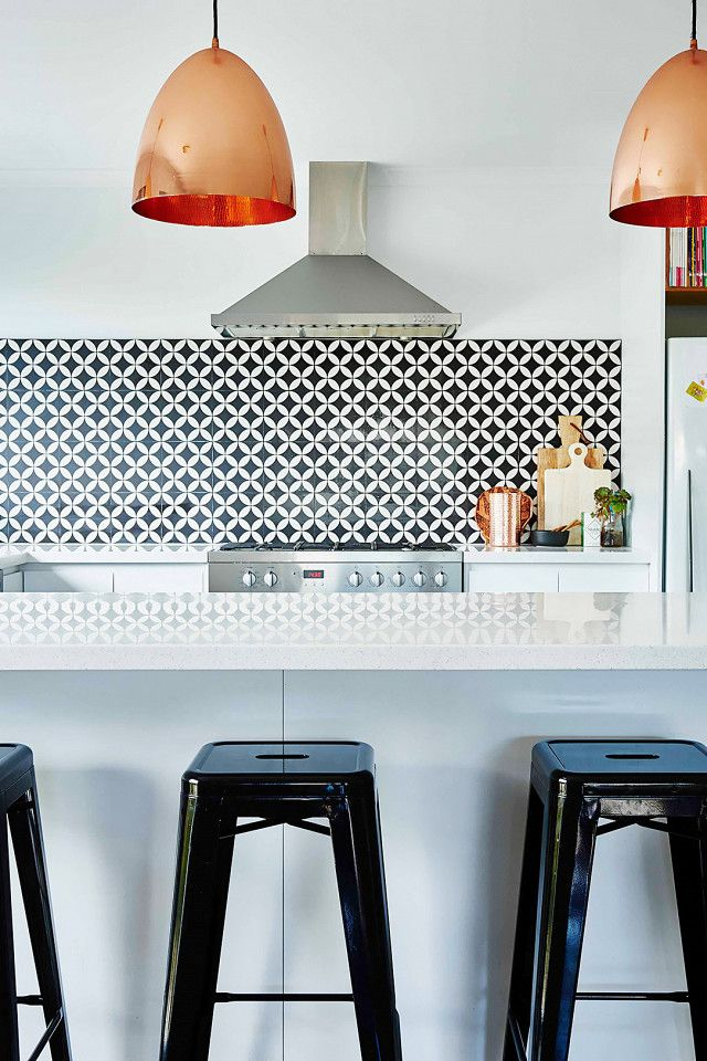 Modern kitchen with black and white back splash, a silver hood, rose gold pendant lights, and black barstools