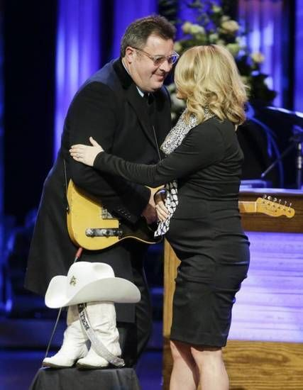 Vince Gill and Carrie Underwood hug after performing a duet during the funeral service for Little Jimmy Dickens in the Grand Ole Opry House Thursday, Jan. 8, 2015, in Nashville, Tenn. In front of them are boots and a hat belonging to Dickens, who died Jan. 2, 2015, at the age of 94. AP photo