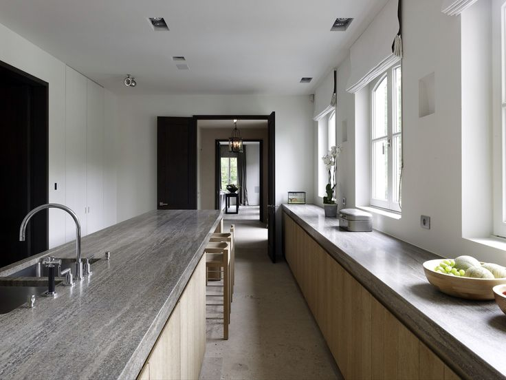 A contemporary kitchen by Obumex… grey bench top with linen cupboards