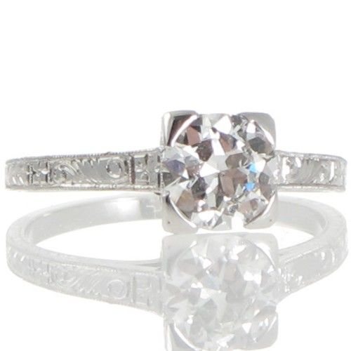 An antique solitaire diamond ring made in 18ct white gold featuring a transition cut diamond of known weight 0.88ct, the four polished corner claws follow down the railed gallery highlighted with pierced scrolling designs all further engraved with patterns of scrolling vines flowers and feathered leaves that follow down and around the upswept shoulders and band leaving a plain polished back. #Rutherford #Melbourne