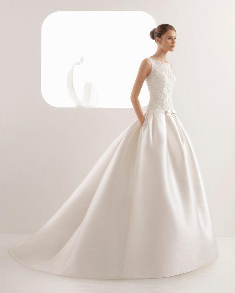 Espetacular vestido de noiva com um favorecedor modelo de cintura descaída. Um corpo confecionado em renda e brilhantes torna o vestido numa joia.