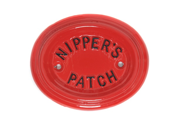 A small bright red, heavy rimmed oval house sign for a pet. The little 'Nippers Patch' small text really makes this dainty garden pet sign.
