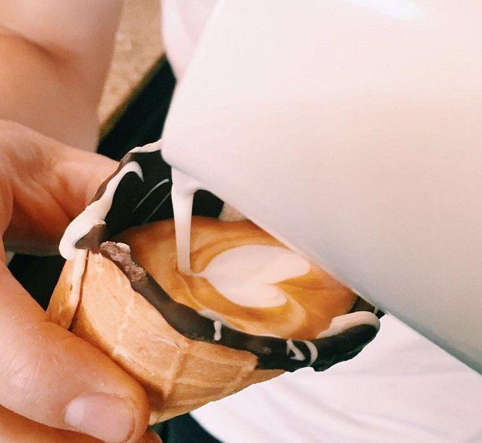 Tem gente indo longe na criatividade com as casquinhas de sorvete. A mais nova onda, lá na África do Sul, é tomar café na casquinha! Recheada de chocolate para dar mais consistência à massa da casquinha, Dayne Levinrad, barista do The Grind Coffee Company, finaliza sua criação com espresso macchiato, o nosso clássico pingado. O resultado é um mix entre o amargo do café e o doce do chocolate na casquinha, hmmmm! E o melhor é devorar a casquinha achocolatada com café! Um vídeo publicado por…