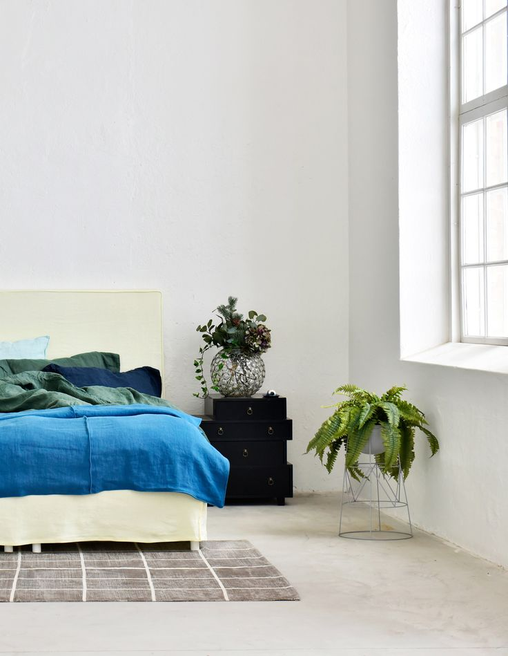 Industrial loft style apartment with huge windows | modern minimal bedroom | pale yellow headboard and bedskirt with a bright blue bedspread | IKEA Abelvär headboard with a Bemz cover | Did you know that Bemz offers a wide range of bedroom textiles