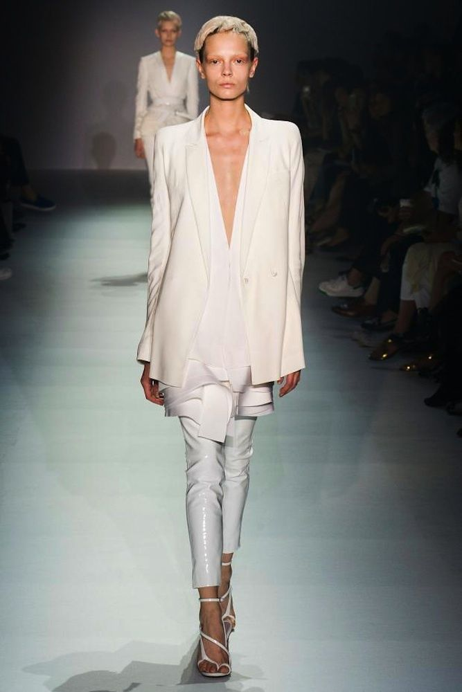 Vestidos de pasarela para novias no convencionales. Haider Ackermann.  Pantalón pitillo de cuero brillante, camisa con acabado de ruffles y blazer largo. Todo en color blanco.