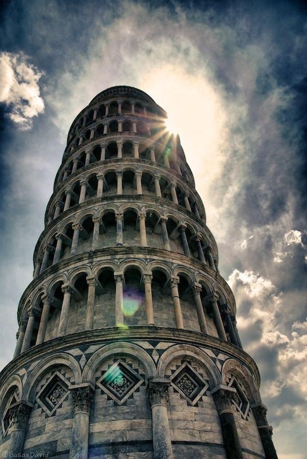 Una de las maravillas del mundo, la torre inclinada de Piza en italia, el sol lo ilumina y las nubes lo acompañan.