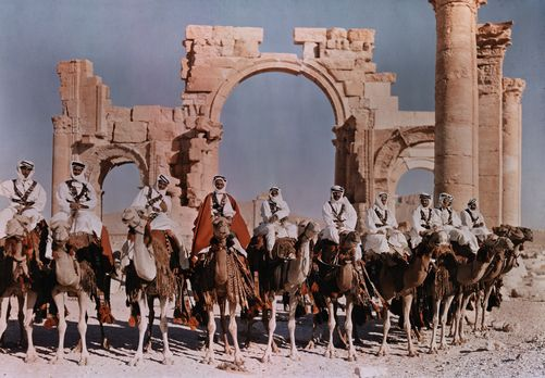 Autochrome: W. Robert Moore. Natives lines up their camels to ride before the gateway at Palmyra. Palmyra, Syria.